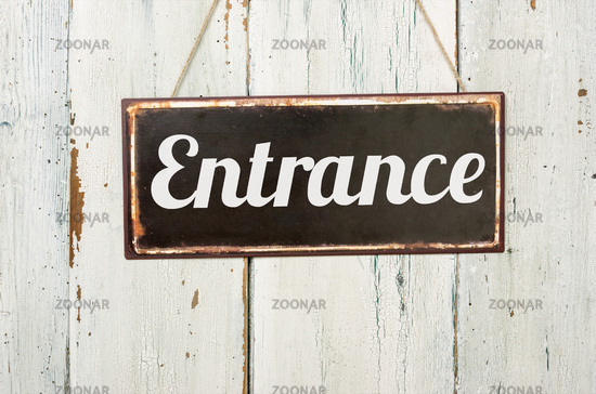 Old metal sign in front of a white wooden wall - Entrance