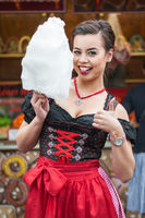Attractive young woman wearing a traditional Dirndl dress with cotton candy floss at the Oktoberfest.