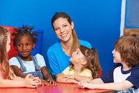 Kindergärtnerin mit einer Gruppe Kinder