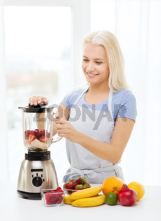 smiling woman with blender preparing shake at home