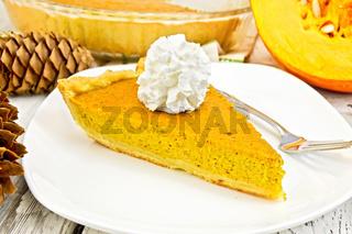 Pie pumpkin in plate with cream on light board