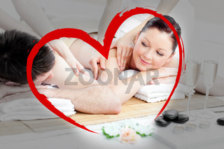 Composite image of relaxing young couple enjoying a back massage