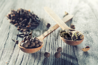 Nutmeg, clove and allspice in old spoon on wooden table