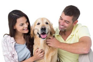 Loving couple stroking dog