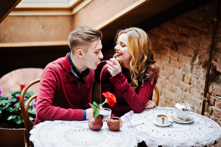 Young beautiful stylish couple in a red dress in love story at the vintage cafe with big windows at the roof