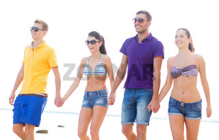 group of happy friends walking along beach