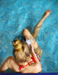 Woman sitting in the pool and using mobile phone