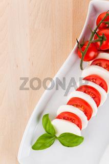 Mozzarellasalat mit Tomaten und Basilikum auf einem Holztisch