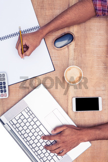 Overhead view of businessman working on laptop while writing on book