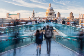 People walking on Millennium Bridge towards St. Paul's Cathedral in London