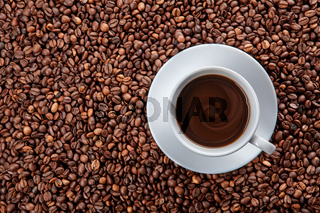 white cup of black coffee on beans