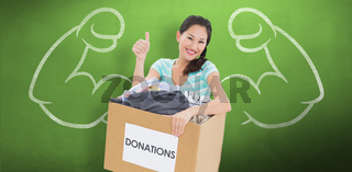 Composite image of woman with clothes donation gesturing thumbs up