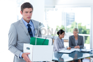 Businessman carrying his belongings in box