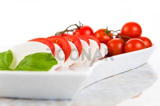 Mozzarellasalat mit Tomaten und Basilikum auf einem Marmortisch