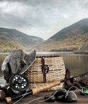 Fly rod with creel and equipment on wood