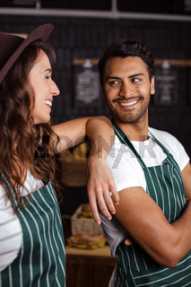 Smiling baristas looking at each other