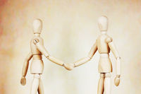 Two men shake hands to each other. Abstract image with wooden puppets
