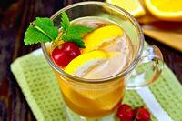 Lemonade with cherry in wineglass on dark board