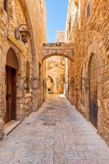Narrow street among old stone walls of Jewish Quarter in Jerusalem, Israel.