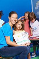 Frau und Kind zeigen Bild im Kindergarten
