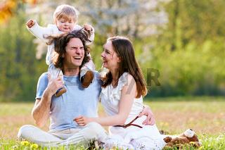 Junge Familie gemeinsam im Gras auf der Wiese