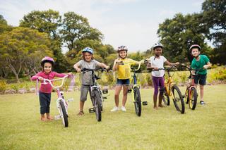 Happy children wearing helmet and posing next to their bike