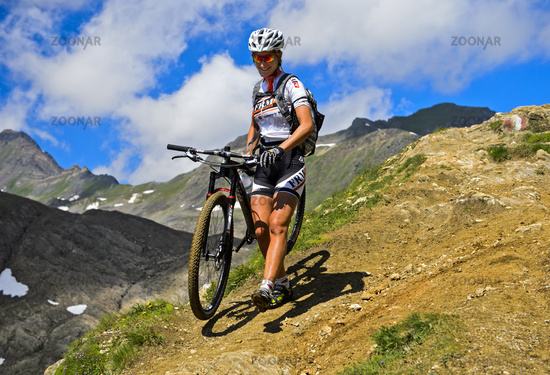Female mountainbiker on a trail in the Alps, Switzerland
