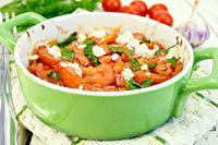 Shrimp and tomatoes with feta in pan on napkin