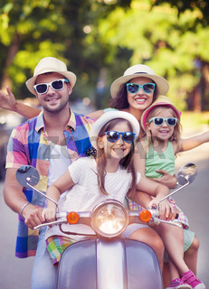 Happy young family riding a vintage scooter in the street wearing hats and sunglasses
