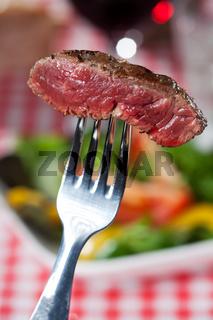 Steakscheibe auf einer Gabel über Salat