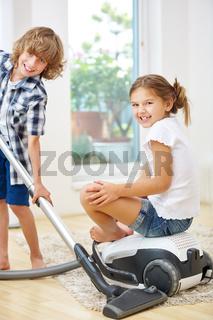 Geschwister beim Saubermachen mit Staubsauger