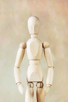 Wooden puppet model against brown background