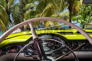 Kuba Innenansicht eines gelben Oldtimers mit Palmen und Blick auf das Meer