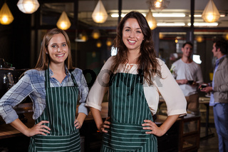 Pretty baristas standing with hands on hips