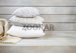 Cozy pillows and plaid on the light wooden background