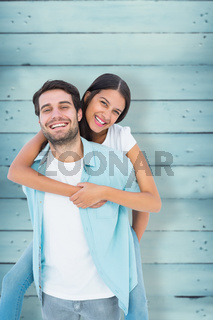 Composite image of happy casual man giving pretty girlfriend piggy back