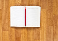 Blank notepad with office supplies on wooden table.