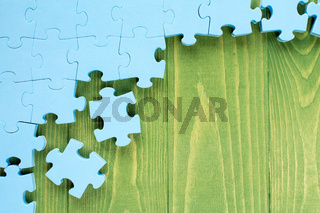 Puzzle on green wooden background