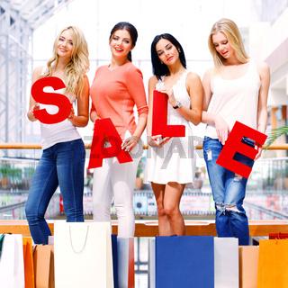 women holding SALE letters