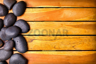 Stones with water drops on the left side on wooden