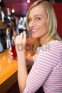 Portrait of happy woman with drink holding straw