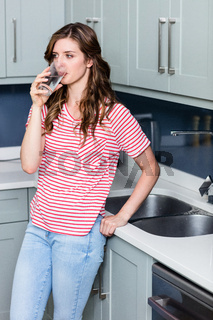 Thoughtful young woman drinking water