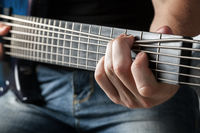 male musician playing on six-string bass guitar