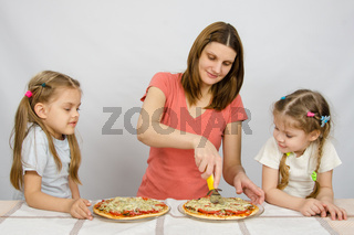 Mom cuts the pizza, and the two little girls eagerly look