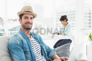 Smiling businessman typing on laptop on couch