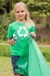 Happy little girl collecting rubbish