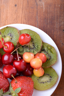 health fruit with cherry, strawberry, kiwi on wooden plate