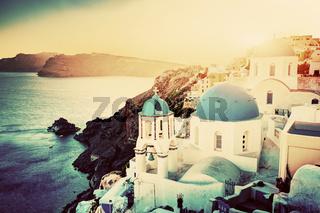 Oia town on Santorini island, Greece at sunset. Rocks on Aegean sea.