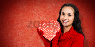 Composite image of smiling woman holding gift box