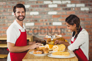 Waiters tidying up pastries on the counter